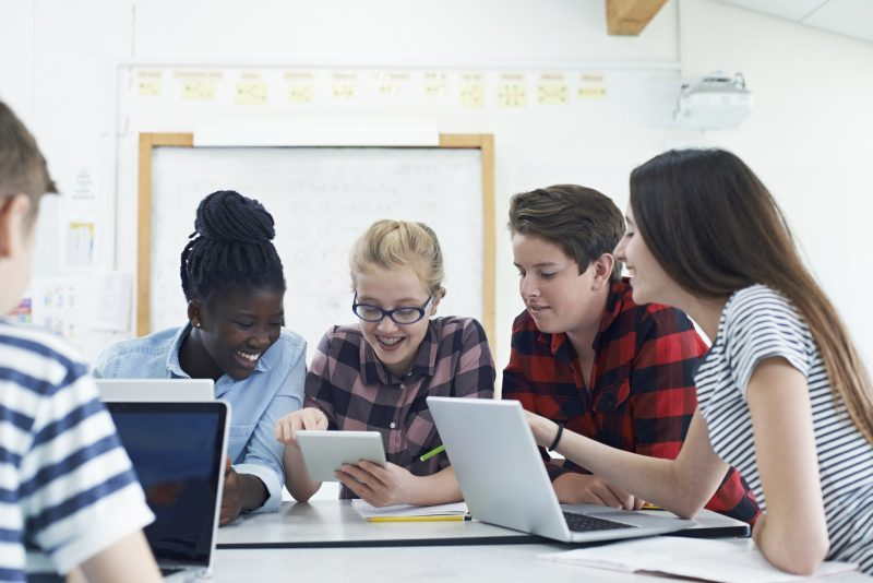 group of teenagers on laptops